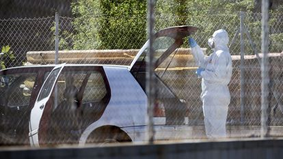 Un agente de la policía científica junto al coche donde se ha encontrado el cadáver de un hombre en la localidad de Roses (Girona), este martes.