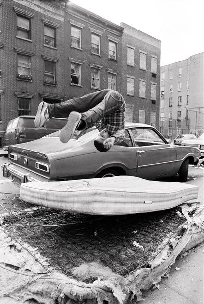 Un chaval se divierte haciendo cabriolas sobre un montón de colchones desvencijados en el Lower East Side.