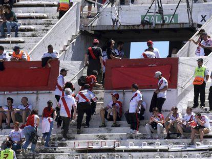 Aficionados de River Plate abandonan el estadio tras confirmarse la suspensión del partido ante Boca.