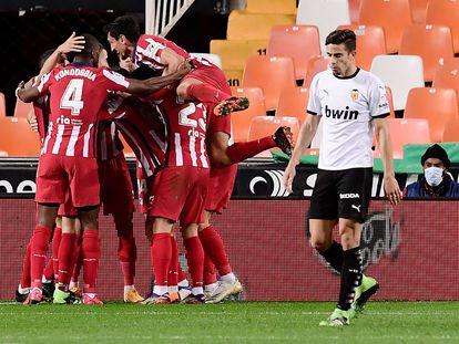 Los jugadores del Atlético celebran en piña el gol en Mestalla este sábado.
