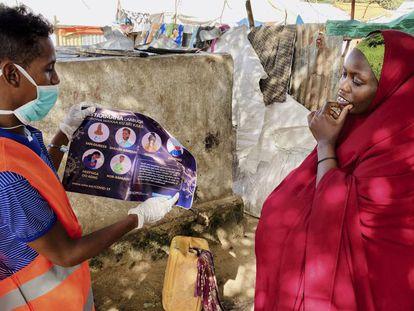 Una mujer residente en el campo de desplazados internos de Weydow, cerca de Mogadiscio (Somalia)  es informada por un trabajador humanitario sobre cómo protegerse para evitar contagiarse de covid-19 el 10 de junio de 2020.