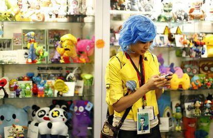 Una mujer disfrazada envia un mensaje de texto desde su móvil en una tienda de juguetes en la Comic Con, en San Diego (EE UU)