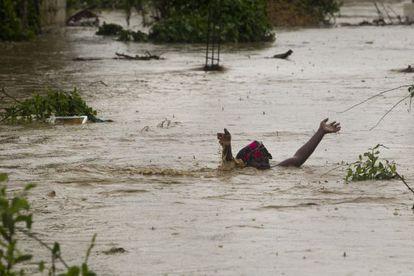 Una mujer avanza por una calle inundada en Puerto Príncipe.
