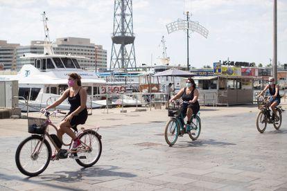 Varias turistas pasean en bicicleta por el puerto de Barcelona.