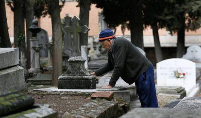 Urbano, de 78 años, limpia una lápida en el cementerio civil de La Almudena, en Madrid.