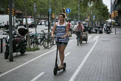 Una mujer circula con un patinete eléctrico por el carril bici de la acera de la Gran Via de Barcelona.