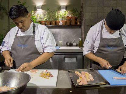 Dos chefs cocinan en un restaurante de Lima.
