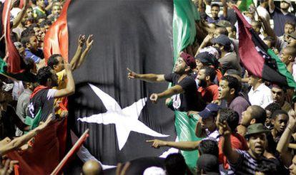 Decenas de libios sostienen una bandera para celebrar la toma de la fortaleza de Gadafi, Bab al-Aziziya, en Trípoli.