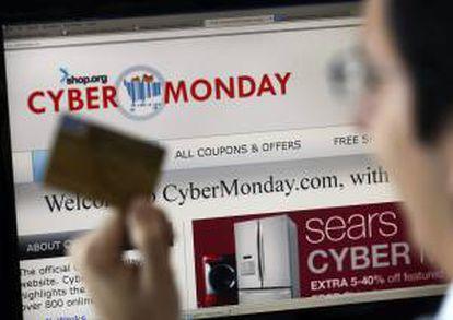 """Un hombre posa con una tarjeta de crédito frente a un ordenador, durante el """"ciberlunes"""" con ofertas en diversas tiendas online. EFE/Archivo"""