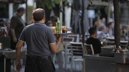 Un camarero sirviendo bebidas en una terraza en Madrid