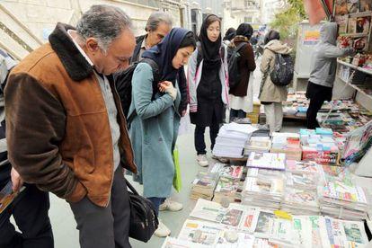 Varios iraníes miran las primeras páginas de los periódicos ayer en Teherán.