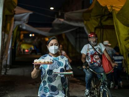 Penélope Ramírez vende postres en medio de la noche en el barrio de Tepito, en Ciudad de México.