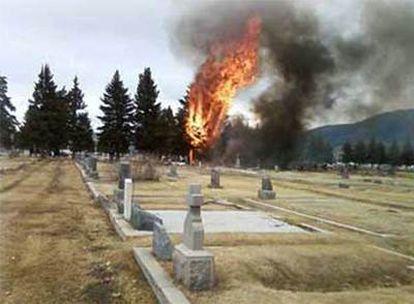Vista del cementerio contra el que se estrelló el avión, con el aparato en llamas al fondo.