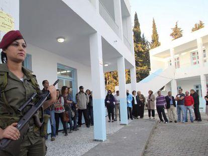 Una mujer soldado resguarda el exterior de un colegio electoral donde varias personas esperan su turno para entrar a votar el domingo.