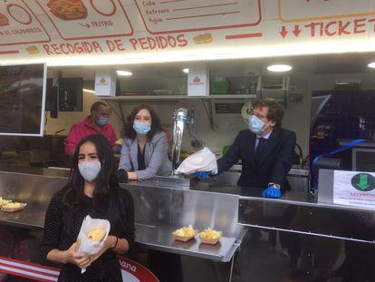 La presidenta de la Comunidad de Madrid, Isabel Díaz Ayuso, y el alcalde de la capital, José Luis Martínez Almeida, detrás del mostrador de un puesto de calamares en el hospital de Ifema. Delante, la vicealcaldesa, Begoña Villacís.