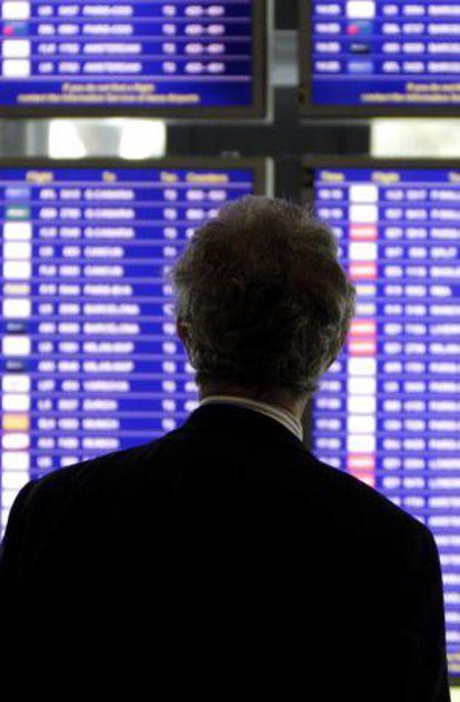 Un viajaero consulta los horarios de los vuelos en un panel informativo del aeropuerto de Barajas, Madrid.