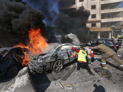 Al menos cuatro personas murieron hoy y un centenar resultaron heridas en un doble atentado perpetrado cerca del centro cultural iraní en el barrio de Bir Hasan, en el sur de Beirut, en un nuevo ataque contra los feudos chiíes. En la imagen, personal de emergencias intentan apagar el fuego tras el atentado, 19 de febrero de 2014.