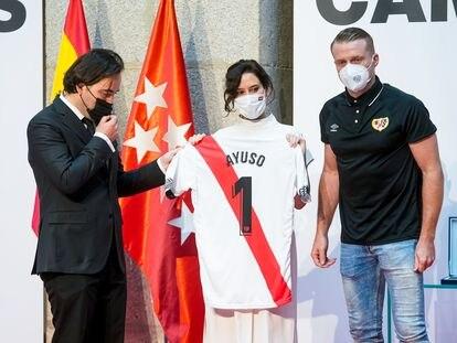 Isabel Díaz Ayuso celebra el ascenso del Rayo Vallecano a Primera con representantes del equipo.