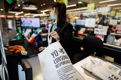 Una cajera guarda productos en una bolsa reciclable hoy, en un supermercado en Asunción (Paraguay).