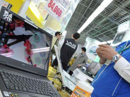 Un empleado limpia un ordenador NEC en una tienda de Tokio.