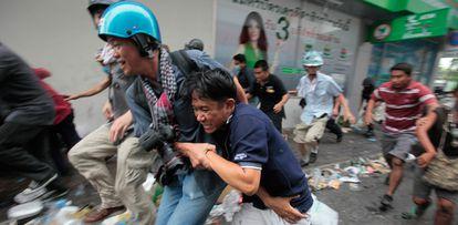 Un fotógrafo ayuda a un manifestante antigubernamental herido por los soldados en el centro de Bangkok.