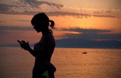 Una mujer revisa su teléfono móvil en la playa de Cabo de Gata en Almería, este verano.