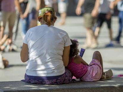 Una mujer y una niña, este lunes en un banco en Sevilla.