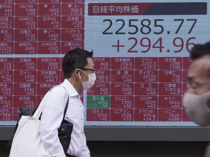 Dos hombres con mascarilla pasan ante un panel que muestra las cotizaciones de la Bolsa de Tokio, en Japón, el 13 de julio.