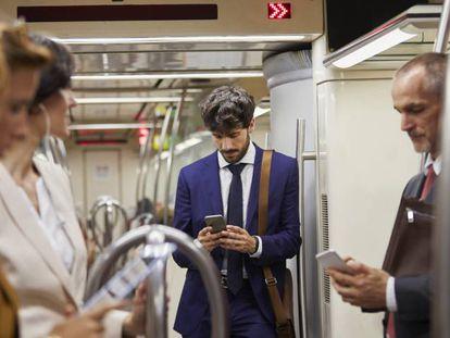 Pasajeros mirando sus teléfonos móviles en un tren de Cercanías.