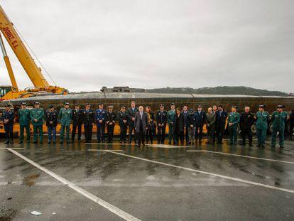 El delegado y la subdelegada del Gobierno en Galicia, Javier Losada y Maica Larriba, acompañados de diversos mandos policiales, ante el narcosubmarino hundido en Cangas (Pontevedra) tras ser reflotado por dos grandes grúas.