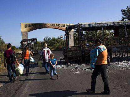 Una familia camina entre autobuses quemados después de un enfrentamiento entre cárteles locales en Michoacán.