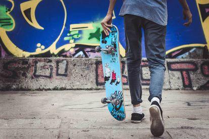 Un adolescente pasea con su monopatín.