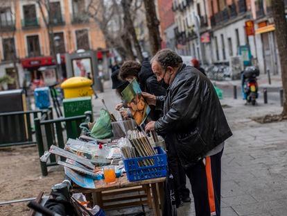 Un vendedor ambulante con mascarilla clasifica vinilos.
