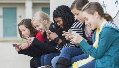 Varias jóvenes ensimadas en sus móviles.