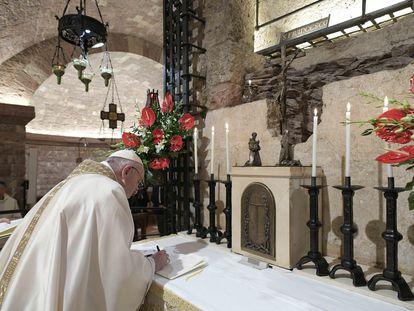 El Papa firma su encíclica en la cripta de la basílica de san Francisco de Asís, este sábado, en una imagen distribuida por el Vaticano.