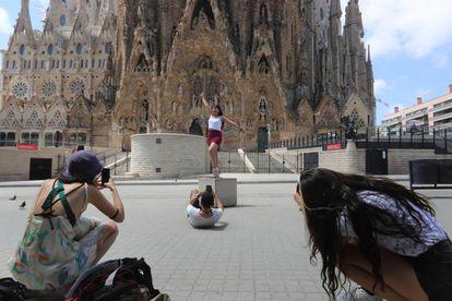 Varios turistas se hacen fotografías frente a la fachada del Naixement de la Sagrada Familia.