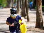 Una niña protegida con mascarilla y una careta de Batman juega con su patinete en la calle.
