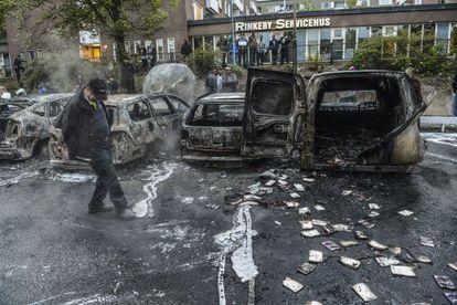 Un hombre camina junto a una hilera de coches carbonizados tras  los disturbios del jueves, en un suburbio de Estocolmo.