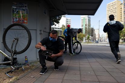 Migrantes venezolanos reparan bicicletas en las calles de Quito, Ecuador.