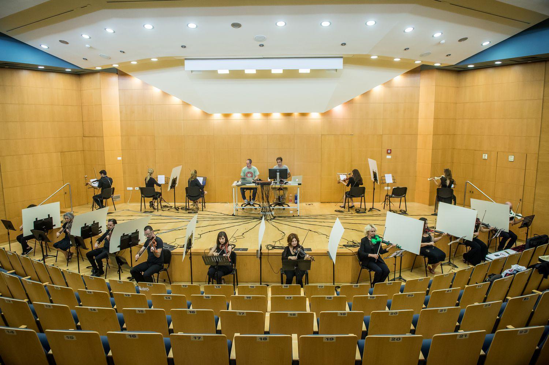 La disposición de todos los violinistas que o bien se dan la espalda o bien les separa una pantalla blanca. En el fondo, Fridman y su compañero controlan la llegada de sonido a los auriculares de los participantes.