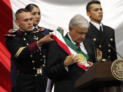Andrés Manuel López Obrador acomoda su banda presidencial tras jurar como nuevo jefe de Estado de México.