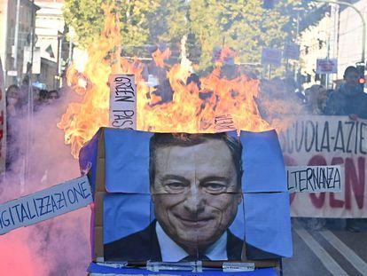 Estudiantes prenden fuego a un póster del primer ministro italiano, Mario Draghi, durante una protesta en Turín convocada con motivo de la jornada de huelga general que vive el país.
