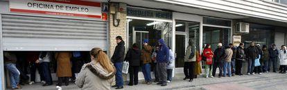 Un grupo de desempleados espera ante una oficina de Empleo de la Comunidad de Madrid.