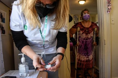 A nurse is preparing to vaccinate a disabled woman at her home, this Monday in New York.