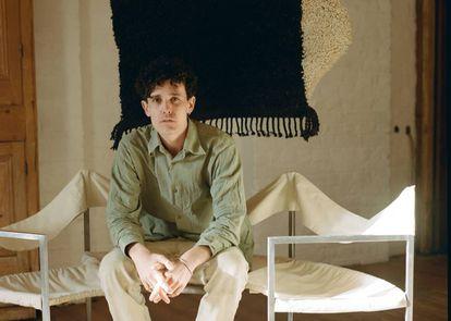 Jermaine Gallacher posa sentado en un banco de Lukas Gschwandtner, delante de su Wavy rug, en negro y crema, una tarde de febrero.  