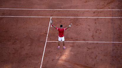 Djokovic celebra su triunfo contra Tsitsipas en la pista central de Roland Garros.