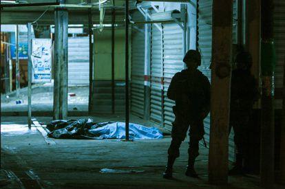 Un militar vigila el sitio donde dos personas murieron tras un tiroteo en Culiacán.