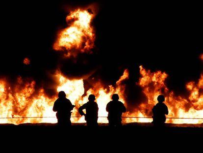 Soldados contemplan el incendio en el ducto de Pemex en Hidalgo.