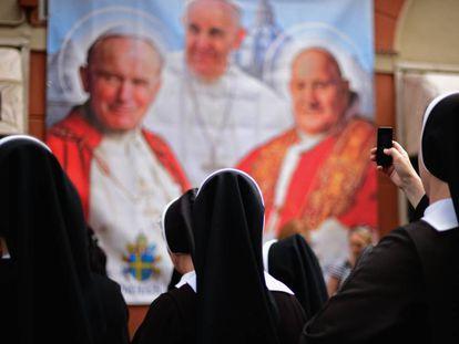 Varias monjas observan y fotografían un panel con la imagen de varios pontífices.