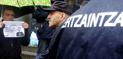Una persona muestra a los ertzainas un cartel con la imagen de Cabacas, durante la concentración de ayer en el Palacio de Justicia de Bilbao.